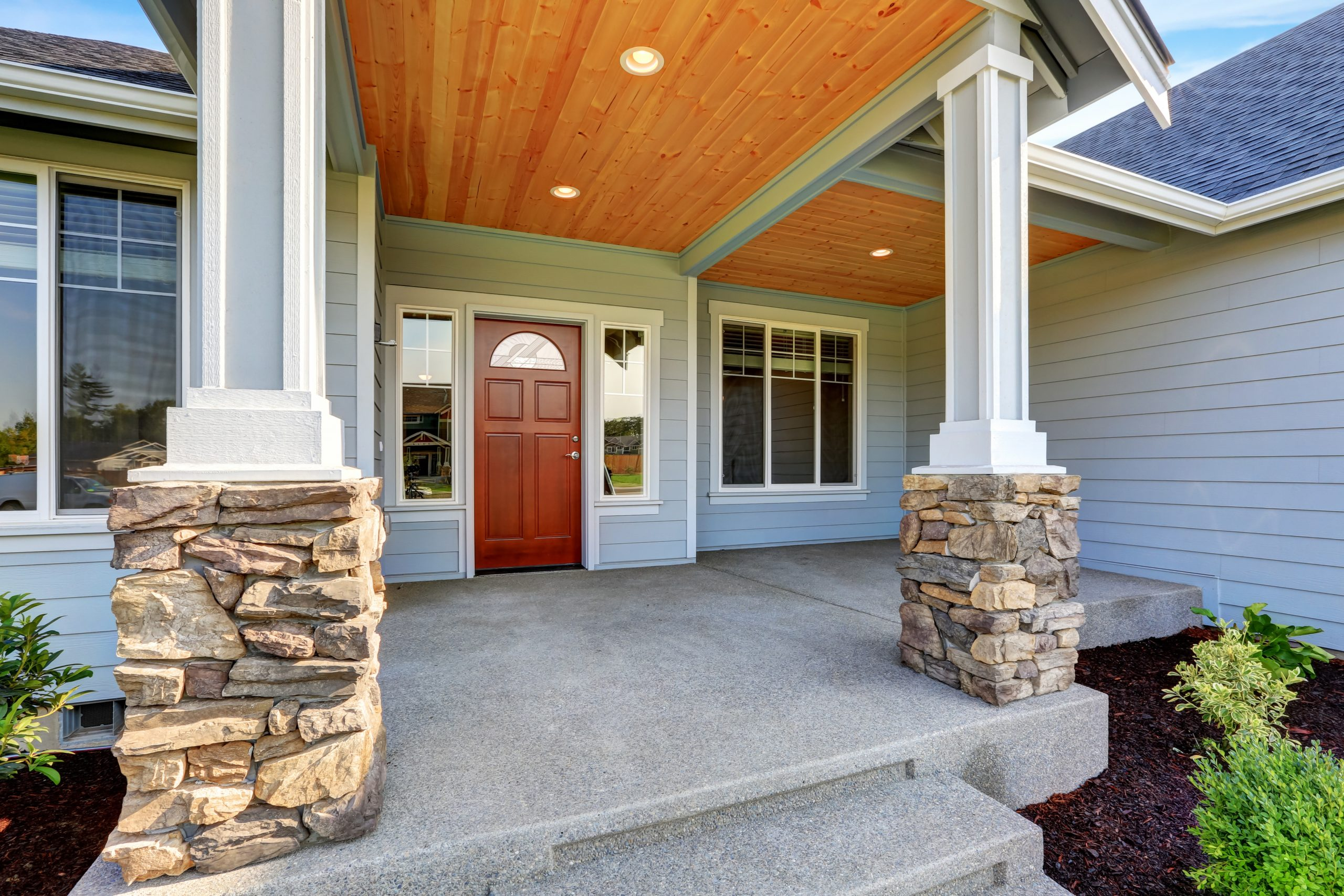Light blue siding house . Porch with stone base columns.